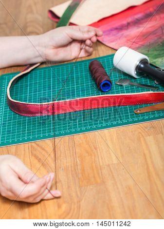 Craftsman Sews New Belt For Leather Bag