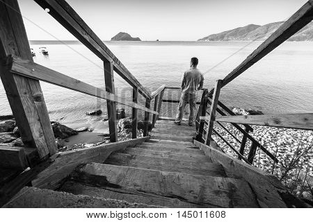 Young Man Stands On Coastal Wooden Stairway
