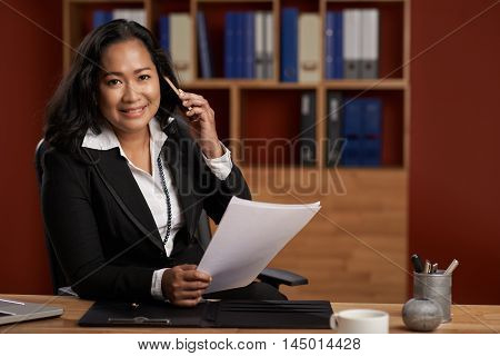 Portrait of smiling Asian lawyer consulting client on the phone