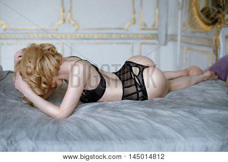 Beautiful Sexy Lady In Elegant Black Panties And Bra. Fashion Portrait Of Model Indoors. Beauty Blon