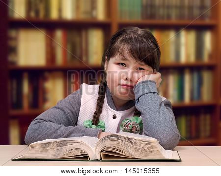 The girl in the library with a book. The concept of overweight teenage complexes difficulties at school