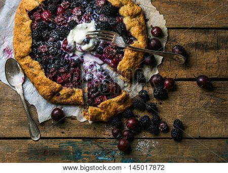 Homemade garden berry galetta or crostata sweet pie with melted vanilla ice-cream scoop on rustic wooden background. Top view, horizontal composition poster