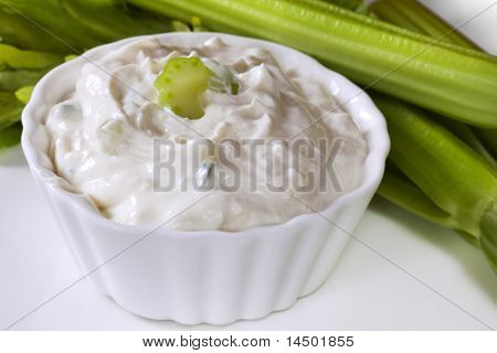 Bowl of tzatziki, with celery behind.  Delicious Greek yoghurt dip.