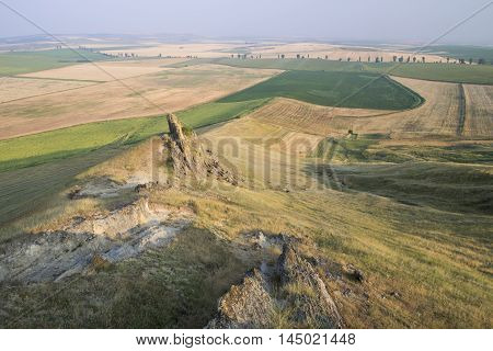 Beautiful rocks on the hill and golden fields natural geological reservation - The Rock with human shape - from Serbesti Romania