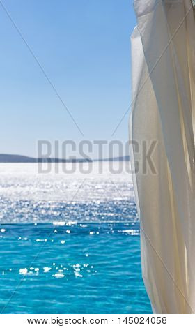 White curtain in front of infinity pool and mediterranean sea