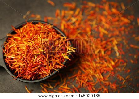 Dried saffron in spoon on table