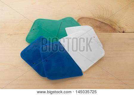 plastic putty spattles on wood background .