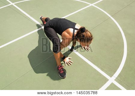 Young woman exercising on basketball court floor insanity workout