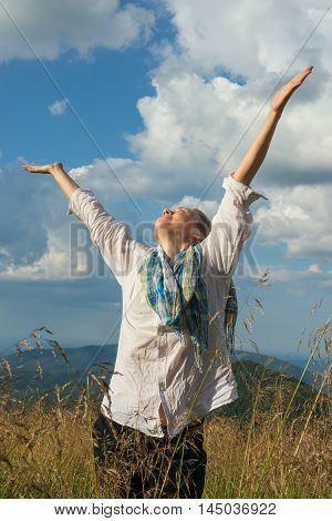 Young woman enjoying life on a mountain meadow. She holds out her hands to the cloudy sky and she is happy