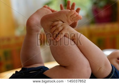 Baby reaching for their own feet and plays with it