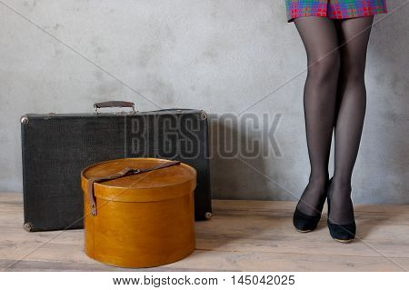 Girl with a suitcase and hat box in an empty room