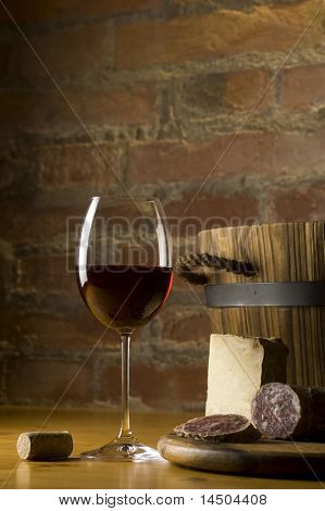 Cutting board with genuine Italian food in a rural kitchen. Red wine glass, ripe hard cheese from ewe's milk and sausage. Warm ray of light in the background. Space for text