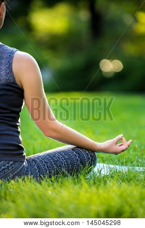 Meditating woman in meditation in city park in yoga pose. Girl relaxing with serene relaxed expression outside in summer. Beautiful young Caucasian female model. Close up