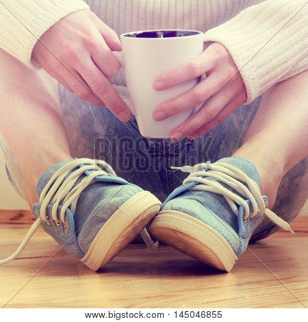 man in sneakers resting with cup of hot drink in their hands / recovering of forces