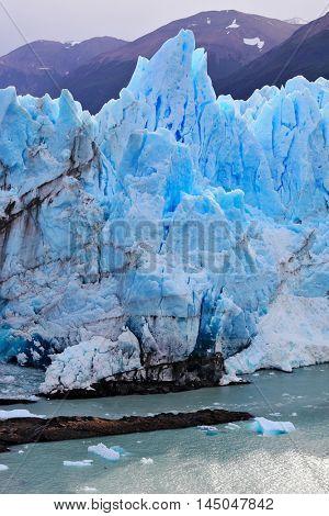 White-blue ice massif multimeter height rises over the lake. Giant lake Perito Moreno glacier