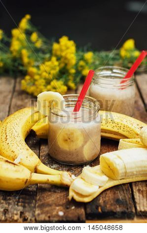 Fruit Smoothies. banana smoothies with milk. Banana Smoothie on a wooden table. Healthy breakfast: banana smoothie with oatmeal. Banana smoothie in glass with fresh fruits on wooden background