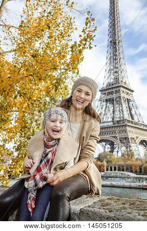 Mother And Child Travellers Sitting On The Parapet In Paris