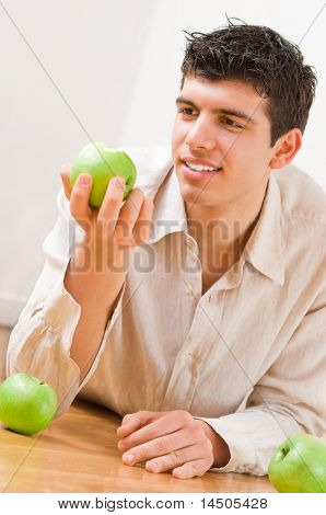 Young man eating green and healthy apples