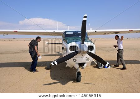 SWAKOPMUND NAMIBIA - JAN 31 2016: Pilot gives instruction to passenger near Cessna airplane on the small airport. Popular tourist attraction in Namibia - flight safaris above Namib desert
