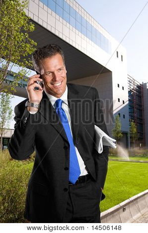 Mature successful businessman talking on mobile outdoor in a business park