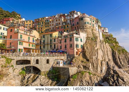 MANAROLA, ITALY - APRIL 11, 2015: People walking on the street of Manarola village in Italy. Manarola is one of five famous coastline villages in the Cinque Terre National Park at the Ligurian sea.
