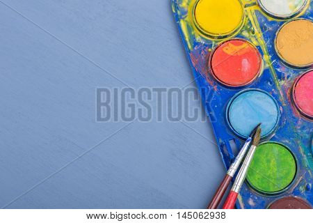 Dirty brushes with paint on a blue wooden background