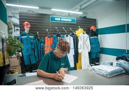 Tobolsk, Russia - July 15. 2016 Sibur company. Smiling storekeeper of SIBUR company gives uniform