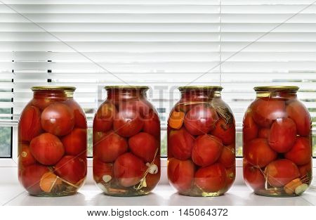 Glass jars with red ripe tomatoes sealed airtight metal lid.