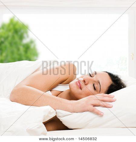 Mooie jonge vrouw slapen op bed in haar slaapkamer thuis in de ochtend