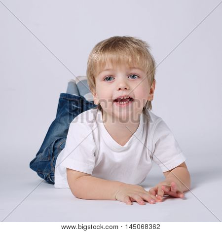 photo of happy boy lying on bright background