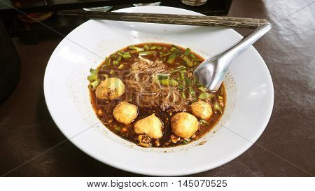 Thai Boat Narrow wet rice noodles pork ball dark soy sauce have morning glory with garlic dill blood pork crackling and pickled chilli pepper in a large bowl of white. And chopsticks made from coconut shell favorite food. Thai people said Boat noodle beca