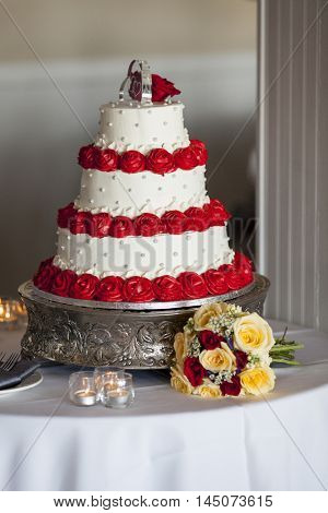 Three tiered wedding cake with red rose confection