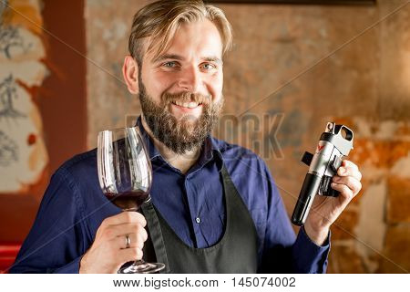 Lviv, Ukraine - August 30, 2016: Smiling sommelier holds Coravin wine system on the wall background. Coravin is patented wine system for pouring wine without taking the cork out of the bottle