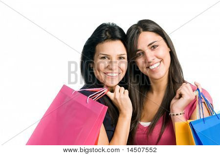 Two beautiful smiling young brunette women doing shopping isolated on white background
