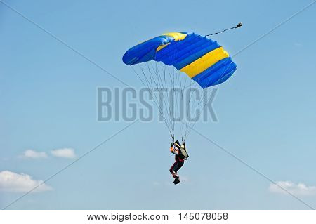 Kharkiv Ukraine - August 20 2016: Skydiver flying on colorful parachute at the airfield Korotych Kharkov region Ukraine on August 20 2016