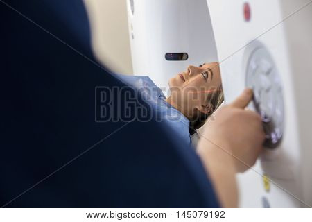Patient Undergoing CT Scan While Doctor Operating It In Hospital