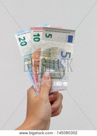 Hand holding three Euro banknotes, white background