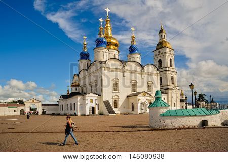 Tobolsk, Russia - July 15, 2016: Kremlin complex. Woman goes near St Sophia-Assumption Cathedral and belltower 1587 foundation year