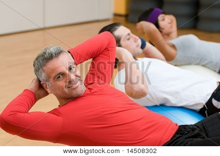 Healthy people with mature instructor doing sit-ups at gym