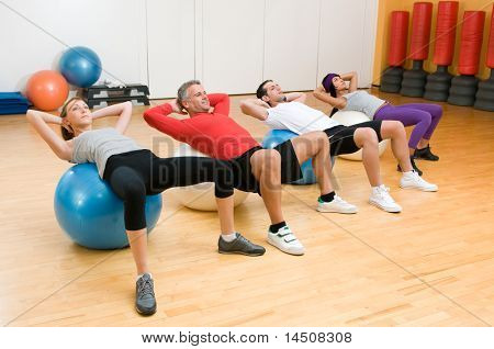 Fitness class making sit-ups on fitness ball at gym, mature instructor in the centre