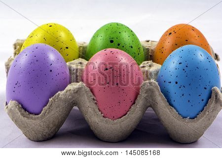 half dozen colored eggs in grey cardboard carton