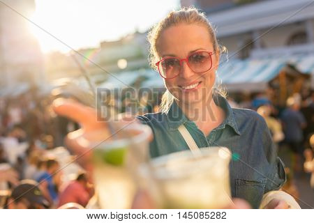 Beautiful young girl toasting outdoors on Open kitchen street food festival in Ljubljana, Slovenia. Popular summer urban tourist event in capital.