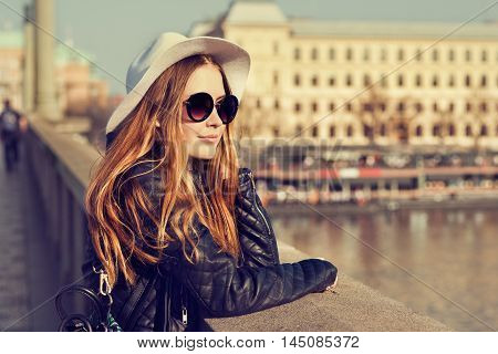 Young pretty hipster tourist cheerful girl posing on the street at sunny day and traveling around european city