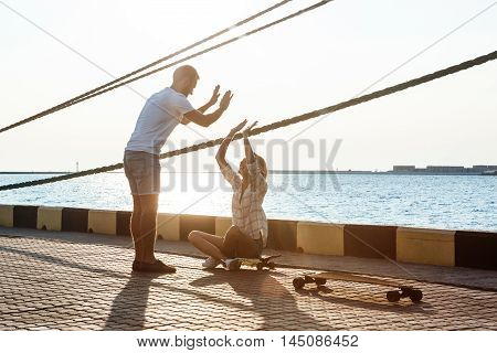 Young beautiful couple walking at seaside, giving highfive, skateboarding. Outdoor background.