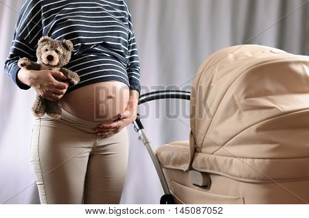 Anticipation of motherhood. Pregnant woman standing near a pram and holding a toy bear on gray background.