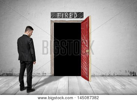 Back view of a businessman standing in front of an open door with darkness behind it and word 'fired' above it. Unemployed. Discharged employee. Losing a job.