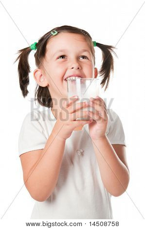 Happy smiling little girl drinking a glass of milk isolated on white background