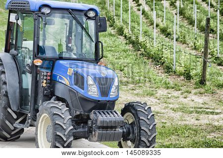 Faenza, Italy: May 29, 2016: Detail of a tractor with a young wineyard background