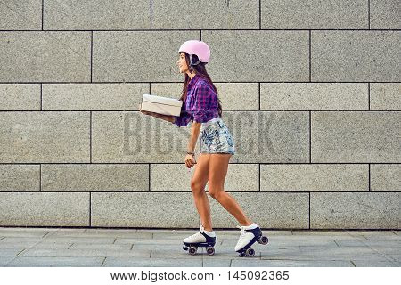 Delivery on roller skates by beautiful girl in helmet. Fast delivery of sportive girl on roller skates. Young woman on roller skates with box or pizza in hands.