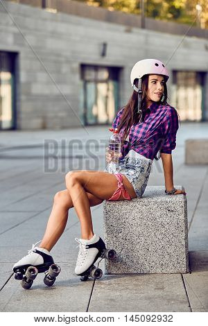 Young woman in roller skates sitting on a concrete bench and holding a bottle of water. Hipster girl resting after active time in urban skate park. Portrait ofbrunette girl in roller skates and helmet